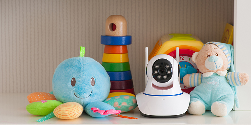 A piece of technology--a baby monitor--on a shelf with baby toys.